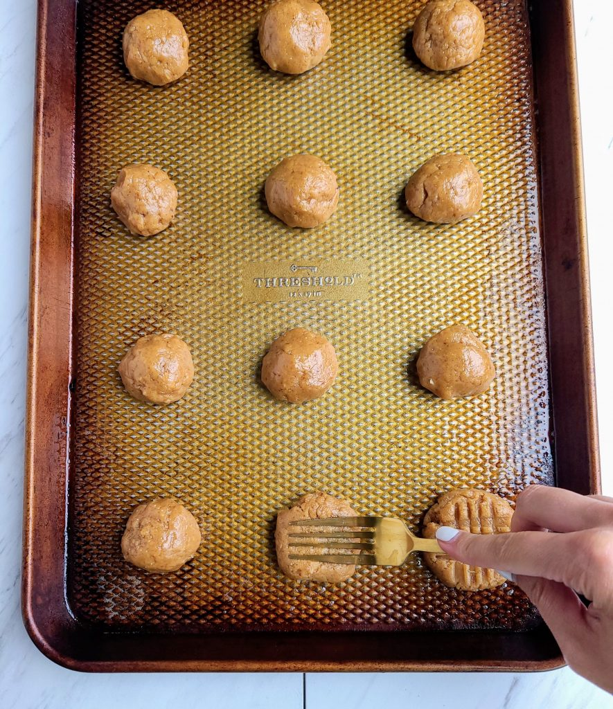 Balls of peanut butter cookie dough on a baking sheet with a fork pressing cross marks into the dough balls