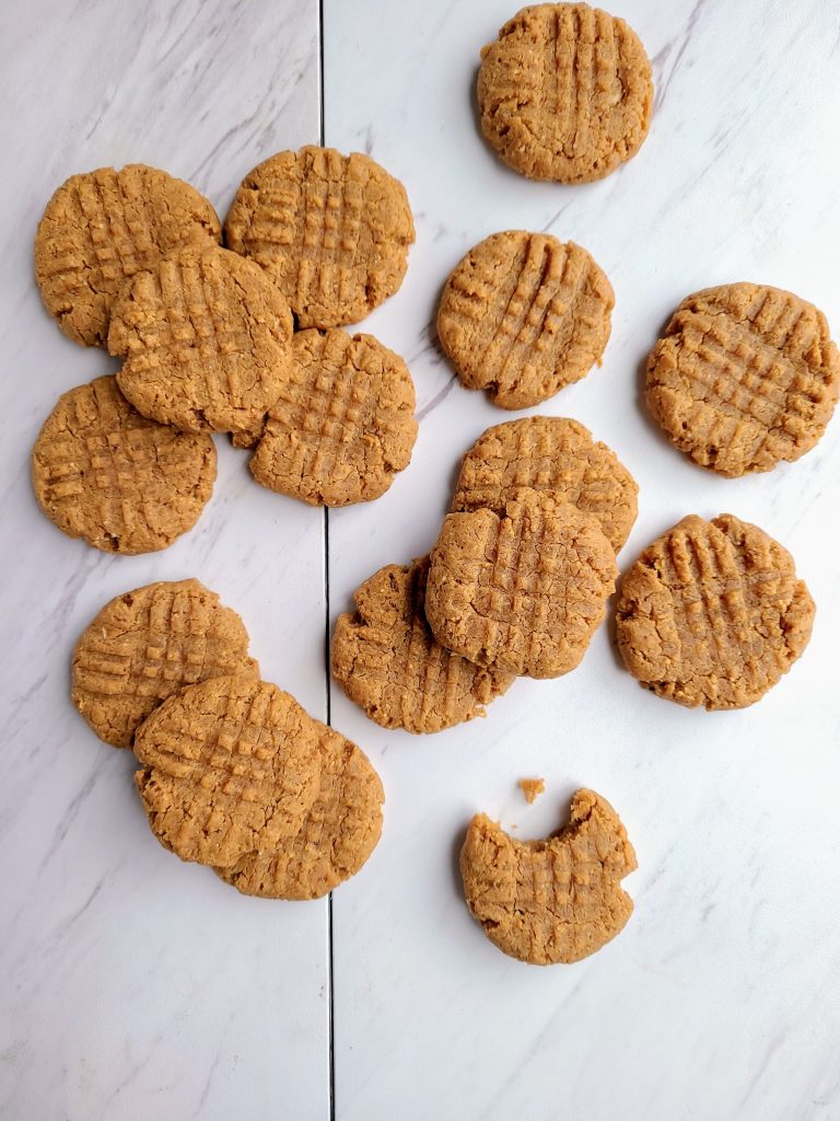 mounds of healthy peanut butter cookies and one with a bite taken out of it
