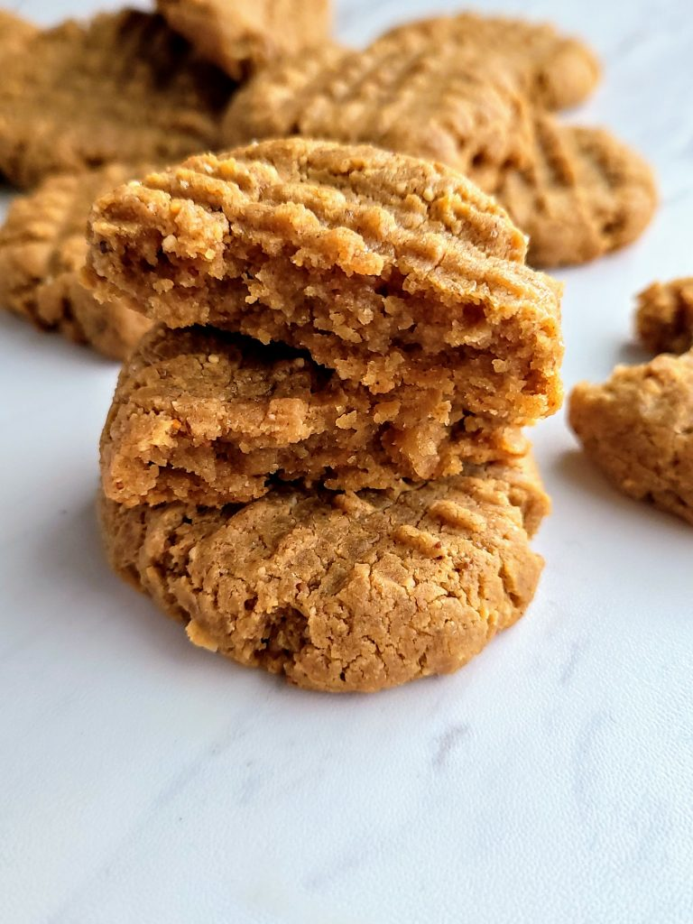 stack of healthy peanut butter cookies, one broken in half and stacked on top of the other