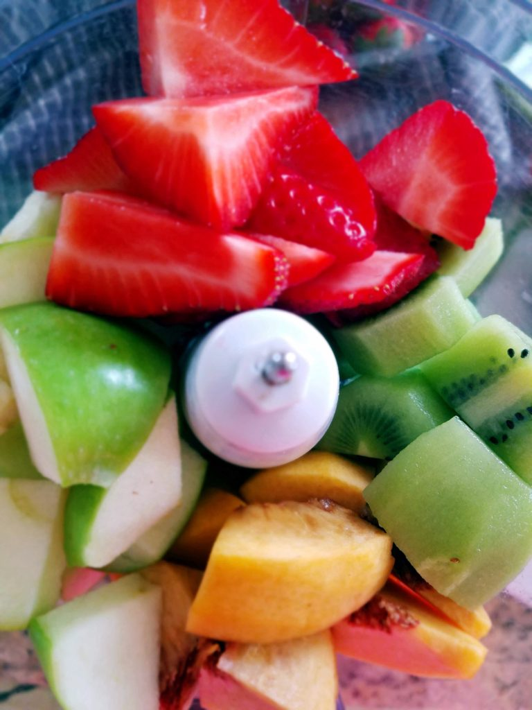 strawberries, apples, kiwi and peaches in a food processor