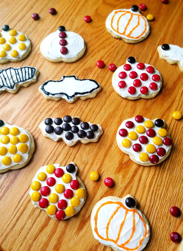 Pumpkin spice sugar cookies are the perfect cut out cookie to make with your kids for Fall or Halloween. Top with cream cheese frosting and M&Ms for decorations.