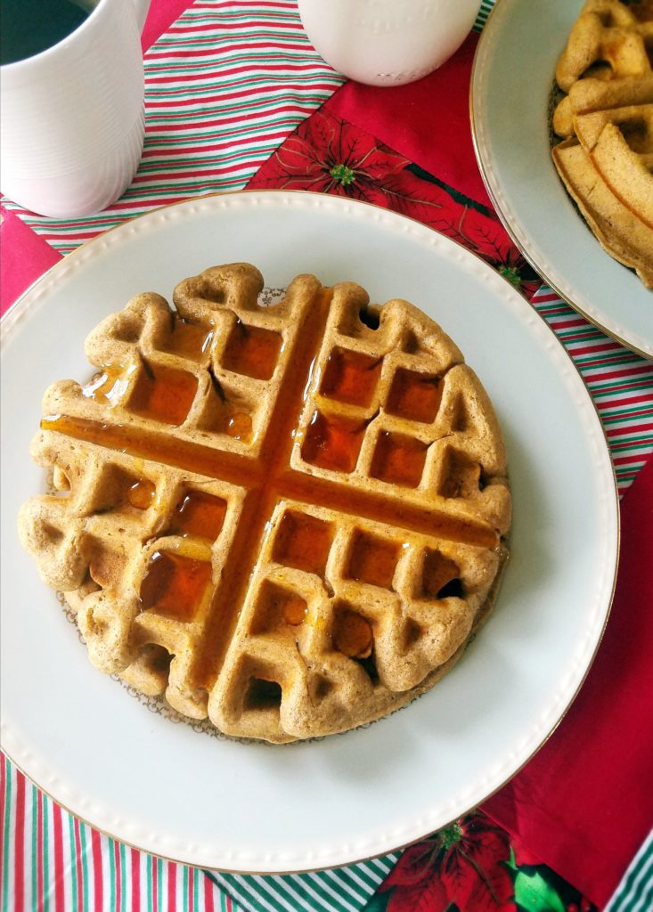 Christmas recipes: eggnog waffles on a white plate with a cup of coffee in the corner