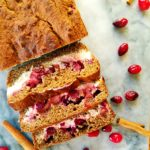 Slices of cranberry cream cheese bread surrounded by whole cranberries and cinnamon sticks