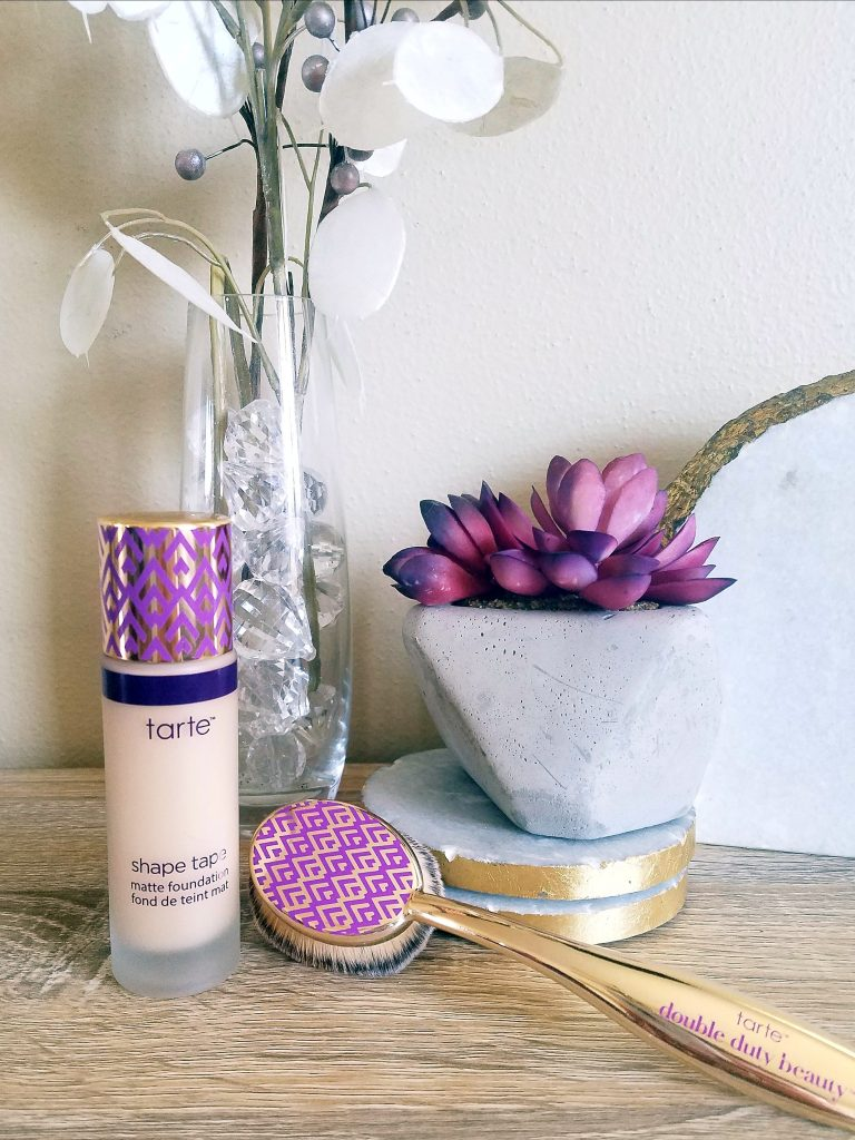 tarte concealer and make-up brush next to flowers
