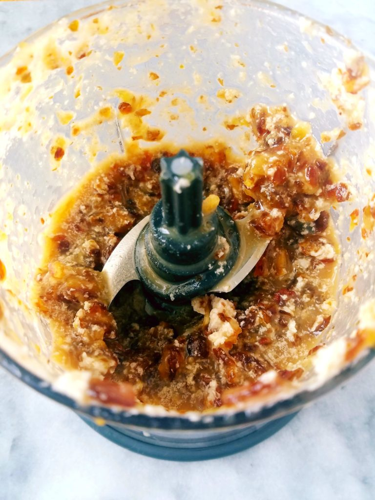 small food processor blending healthy caramel sauce and breaking down the dates