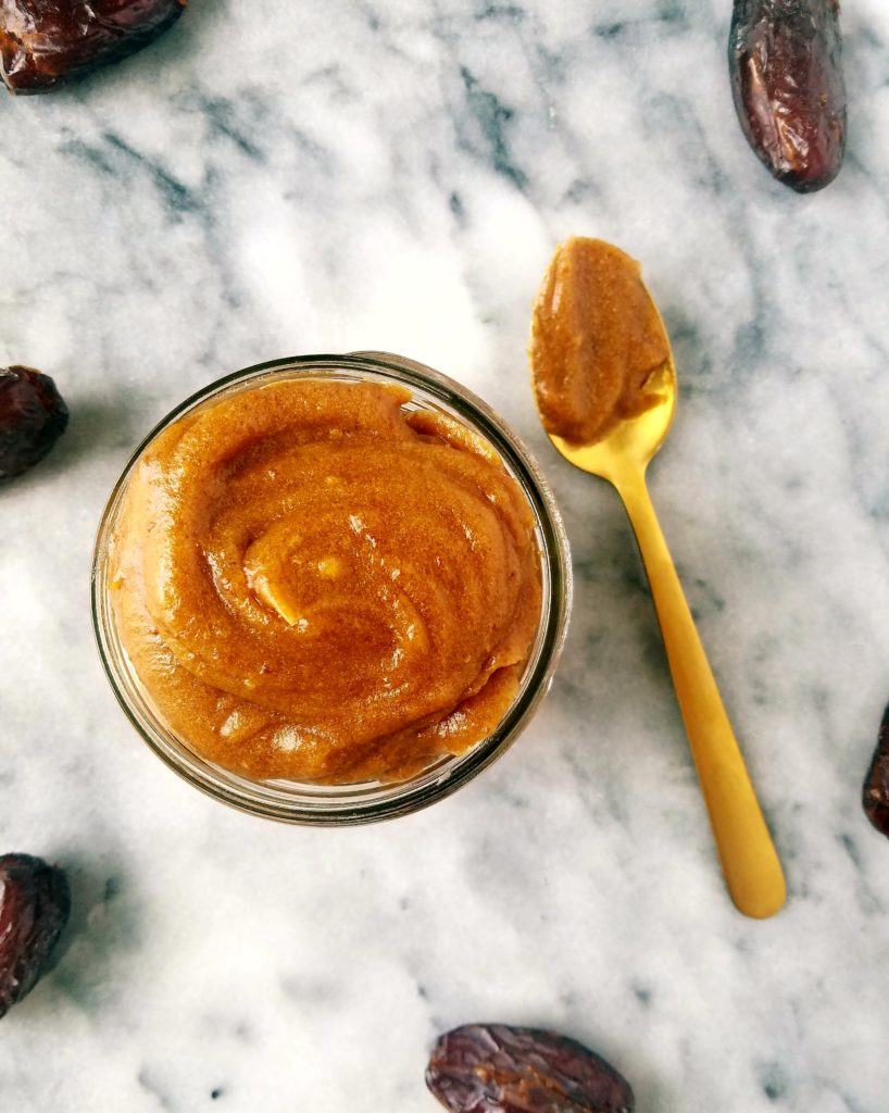 jar of healthy caramel sauce with a spoon to the right with caramel sauce on it