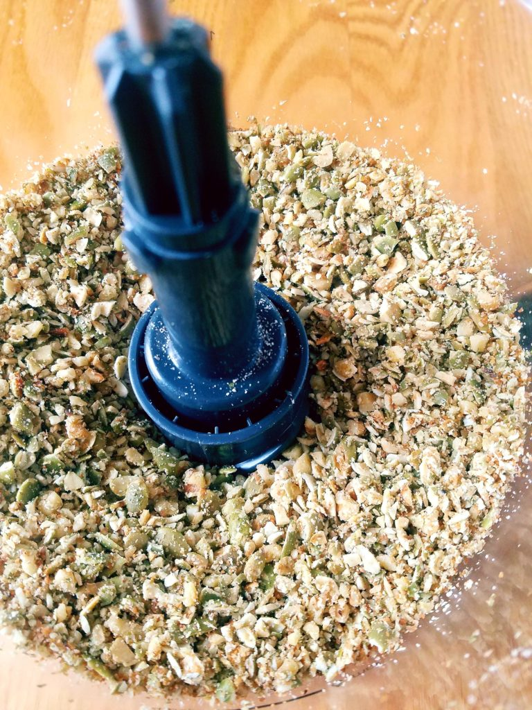 Food processor with blended walnuts, pepitas (pumpkin seeds) and coconut sugar.