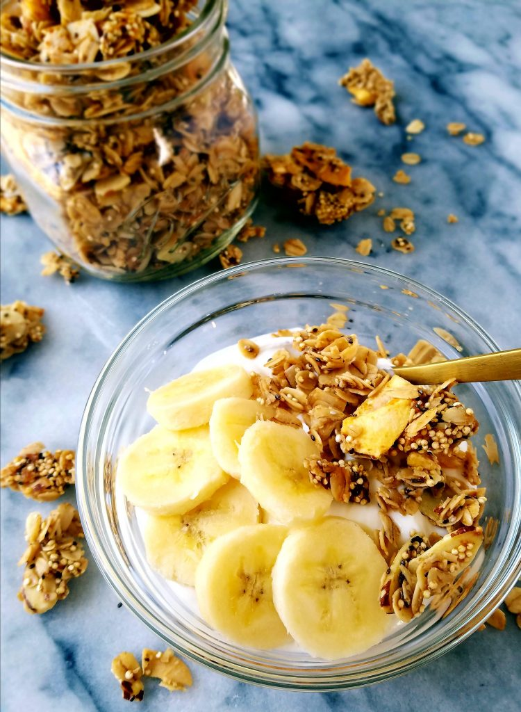 mango coconut granola over yogurt in a bowl with sliced bananas.
