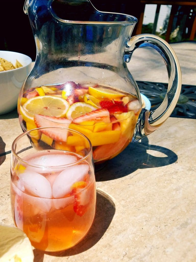 rosé strawberry sangria in a glass with a pitcher behind it