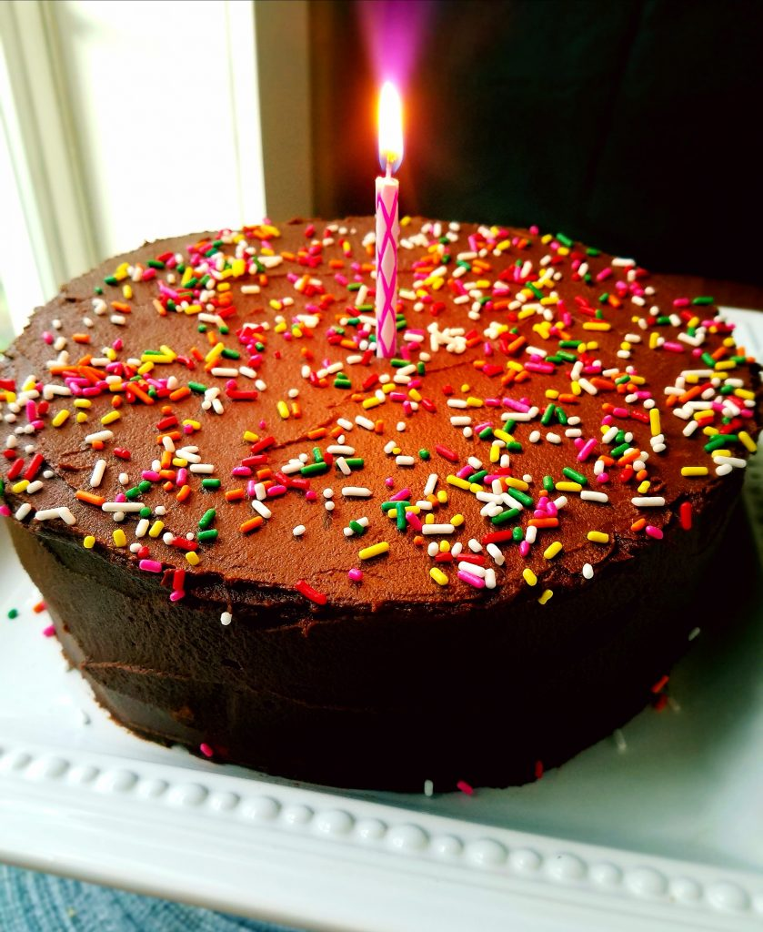 chocolate frosted cake with a lit candle in the center