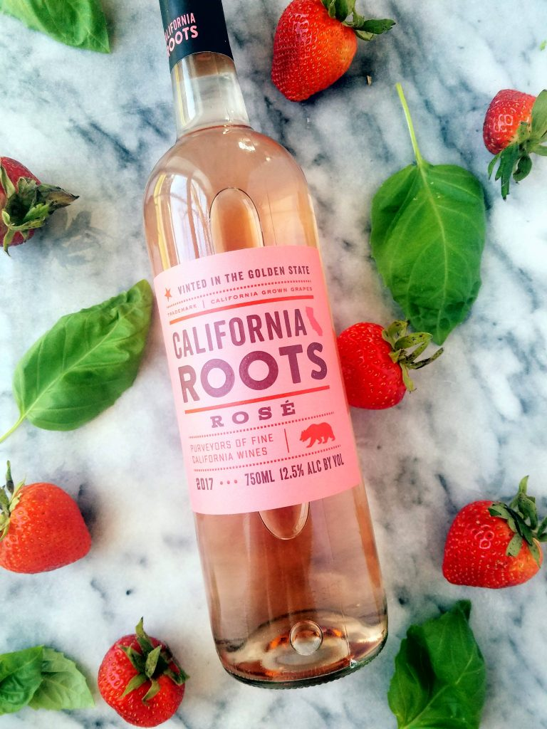 California roots Rose wine with basil and strawberries surrounding it
