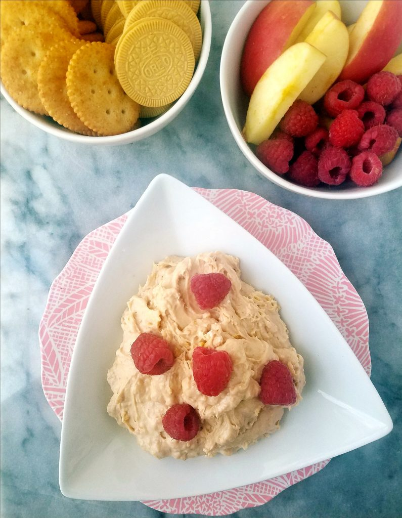 lemon raspberry fruit dip with raspberries on top and fresh fruit and crackers in the background.