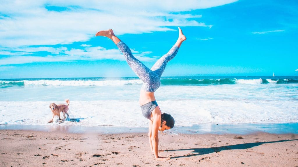 girl doing a split handstand on the beach. How to workout on vacation