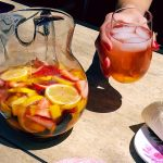 Rosé sangria being held in a glass and in a pitcher