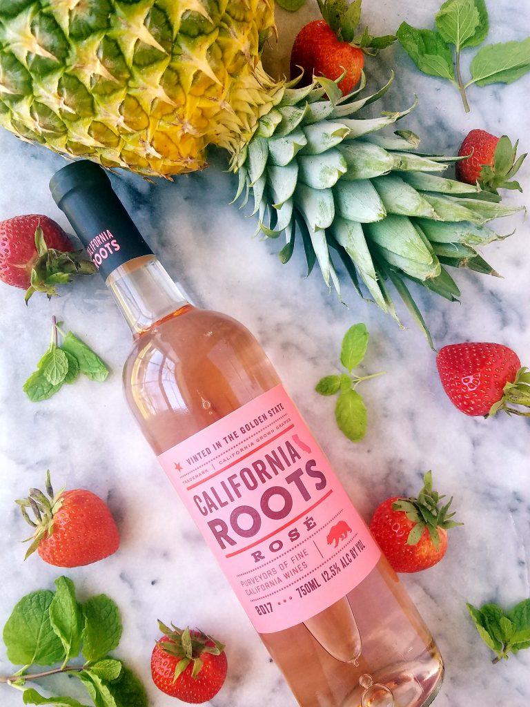 rosé wine surrounded by strawberries and pineapple