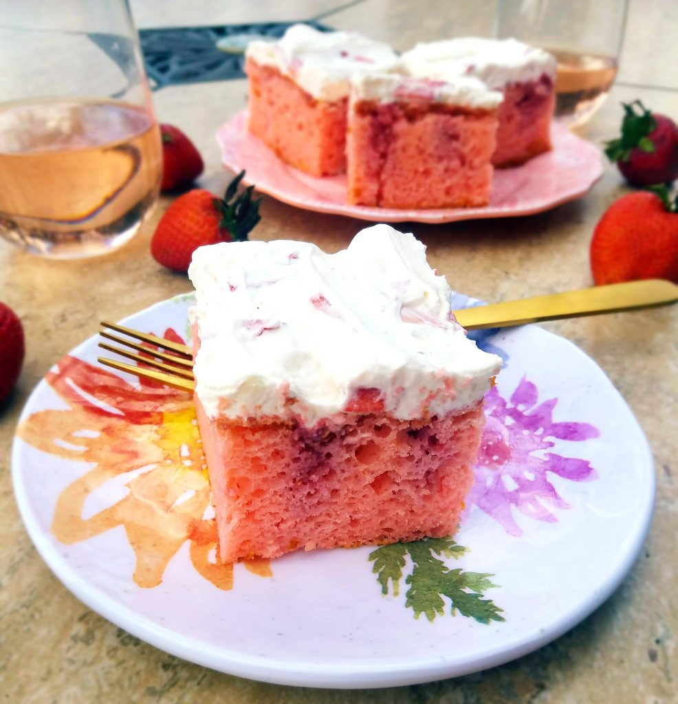 slice of strawberry rosé poke cake and glasses of rosé