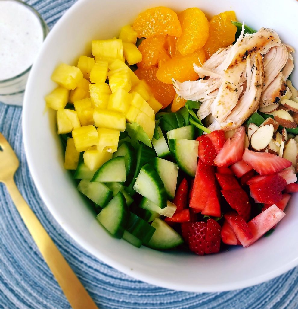 healthy strawberry chicken salad with pineapple, cucumbers and mandarin oranges with homemade poppy seed dressing on the side
