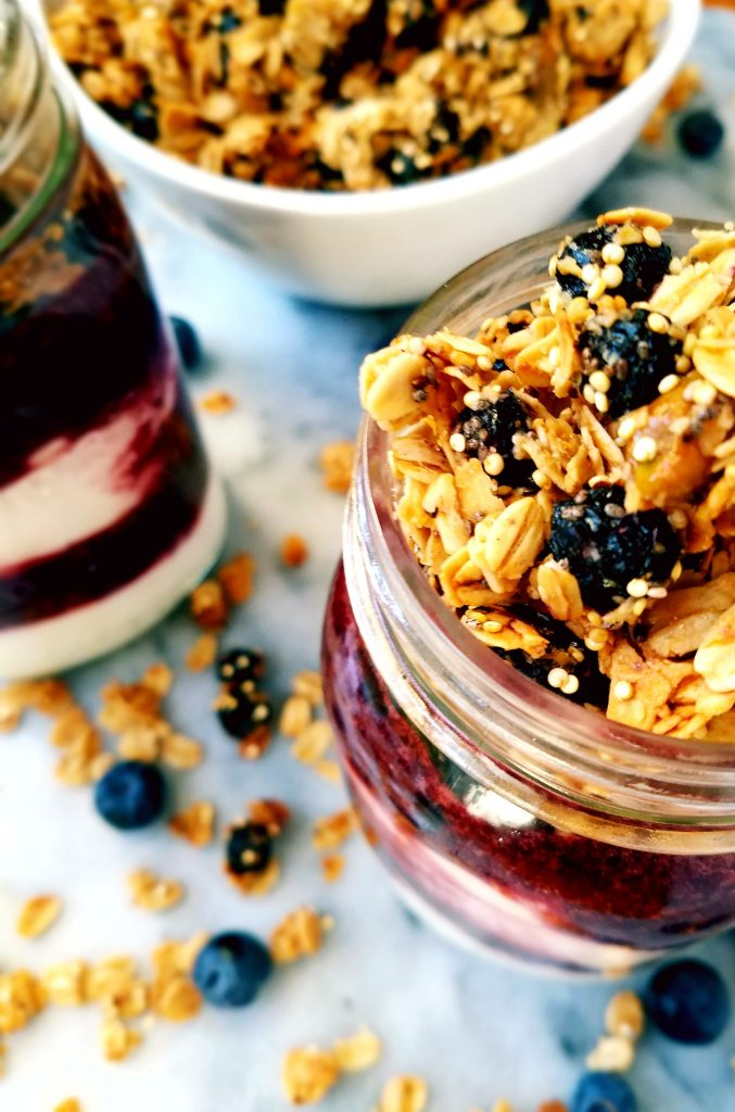 two jars of blueberry and cherry parfaits with granola in the background