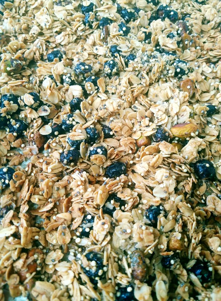 blueberry pistachio granola on a sheetpan