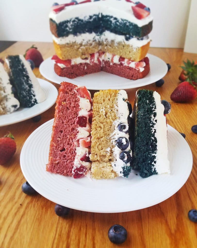 slice of healthy berry layer cake on a plate with cake in background