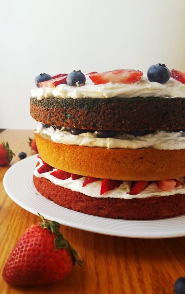 healthy berry layer cake on a white plate