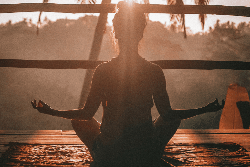 woman sitting on a yoga mat looking at the sunset