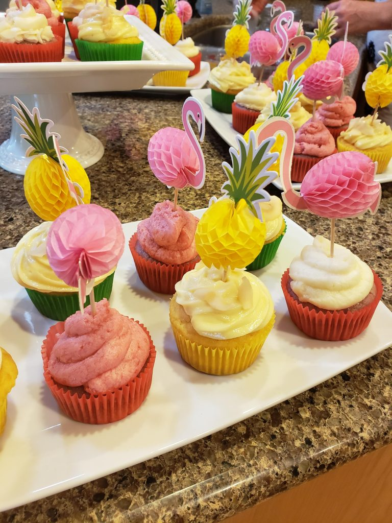 pink and yellow cupcakes with flamingo and pineapple toppers
