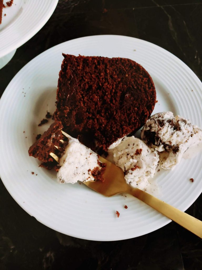 slice of healthy chocolate cake on a plate with ice cream and a gold fork