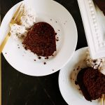 two slices of healthy chocolate cake on white plates with gold forks