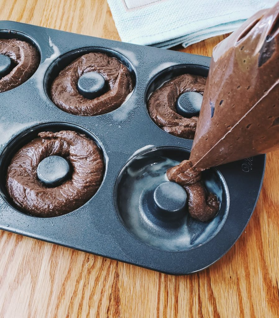 piping donut batter into a donut pan
