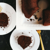 two slices of healthy chocolate cake on white plates with the large cake off to the side