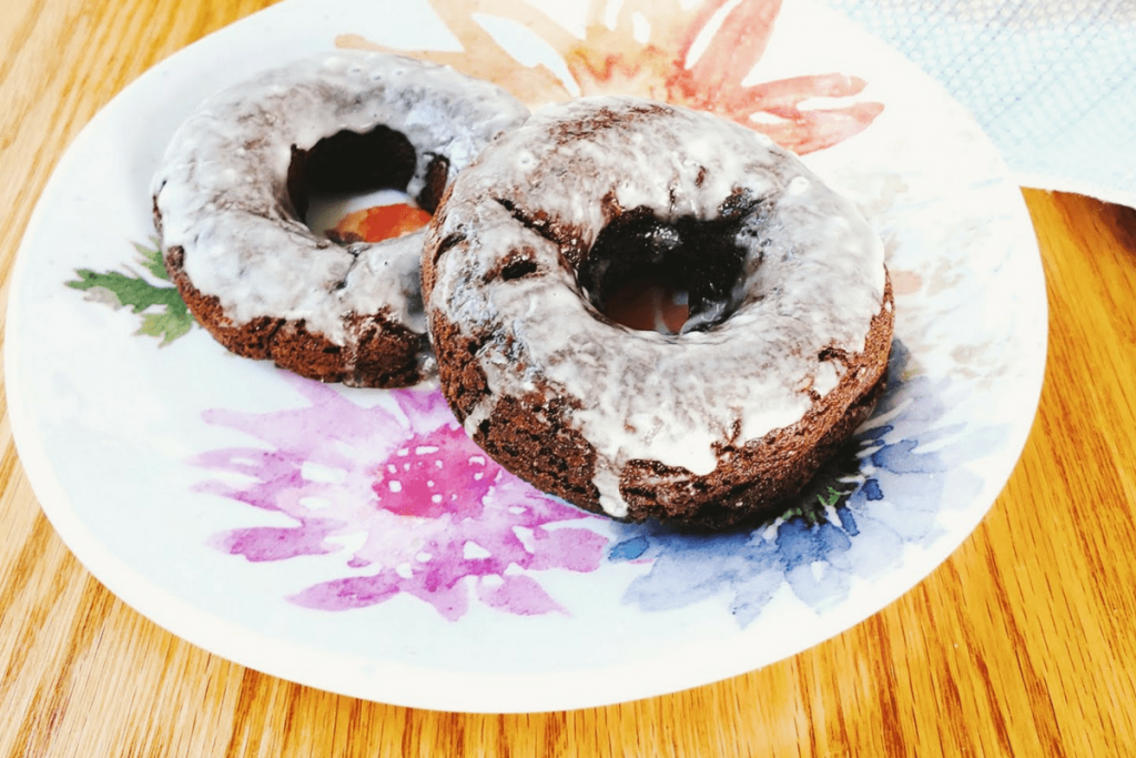 two baked chocolate protein donuts on a plage