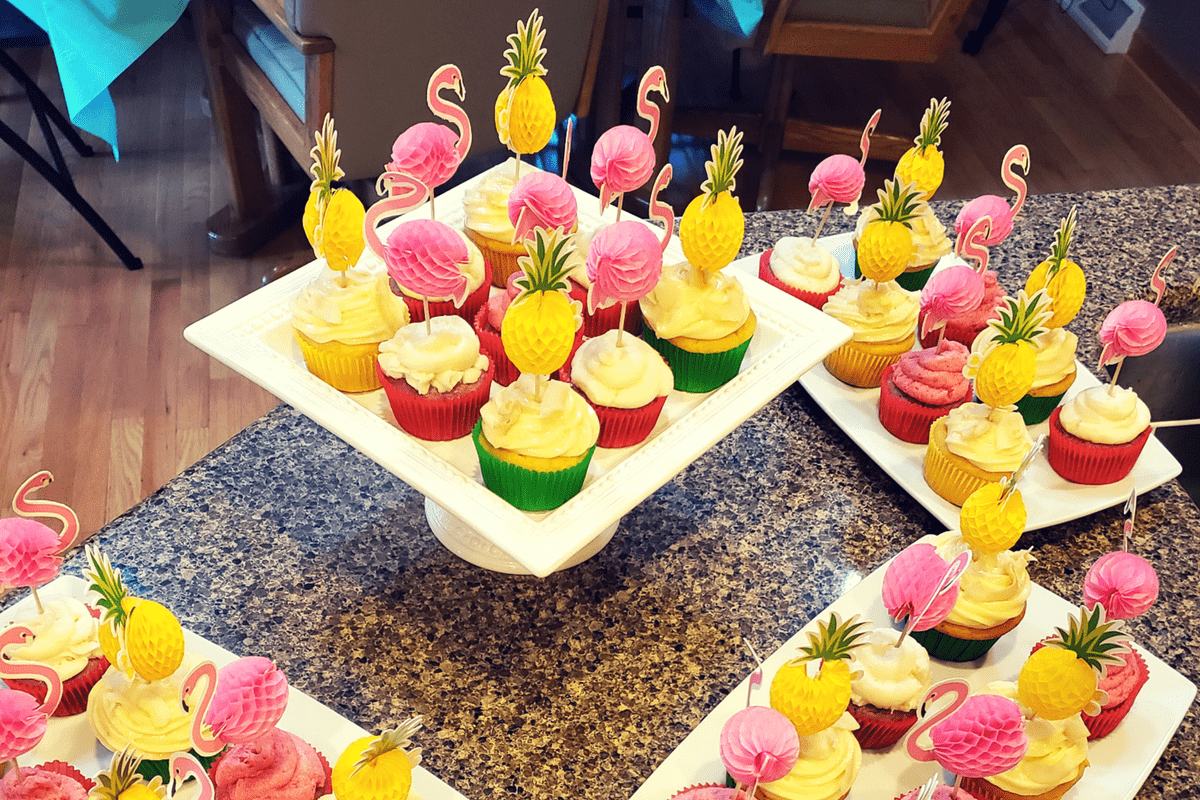 plates of cupcakes with pineapple and flamingo cake toppers