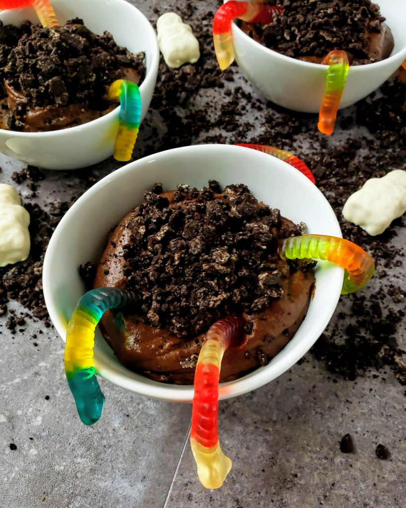 healthy chocolate pudding dirt cups in three bowls with worms in them