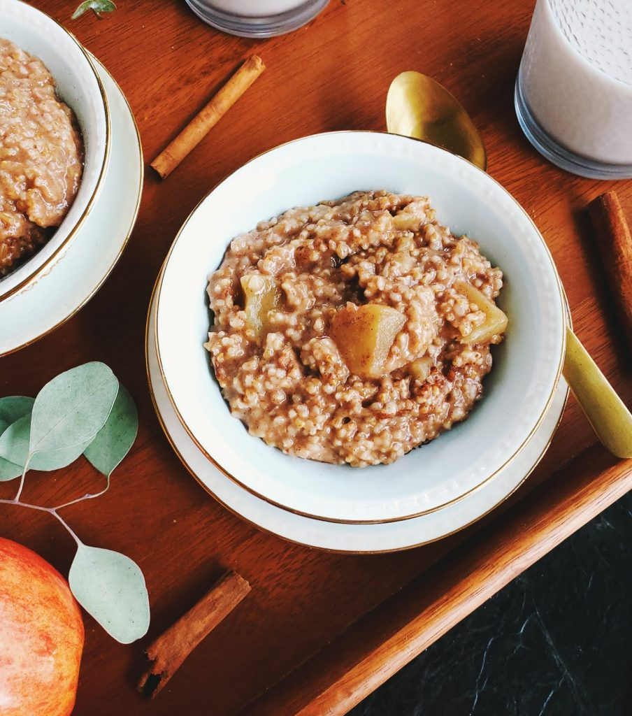 apple pie steel cut oats in a bowl with a gold spoon to the right