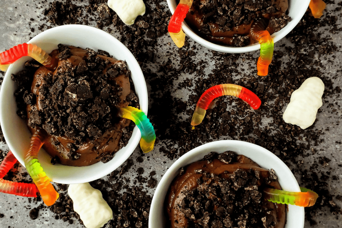 three bowls of healthy chocolate pudding dirt cups with gummy worms in them