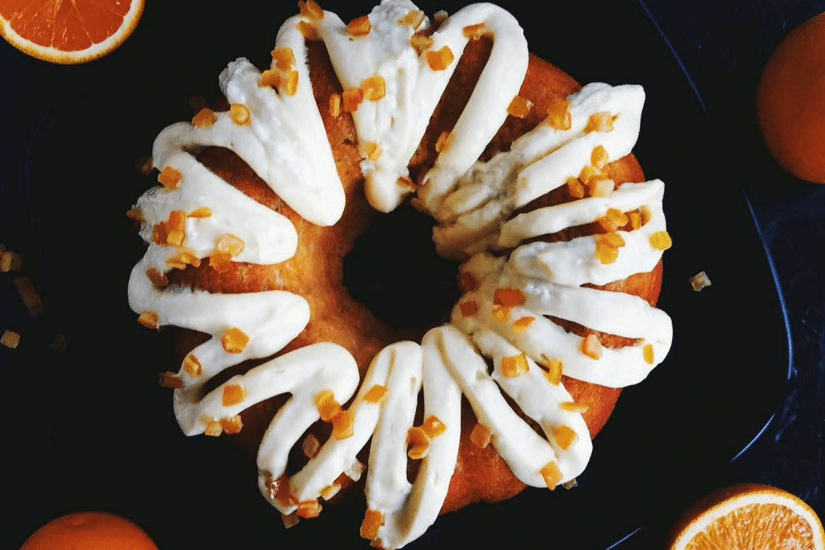 Orange cake on a plate with cream cheese frosting