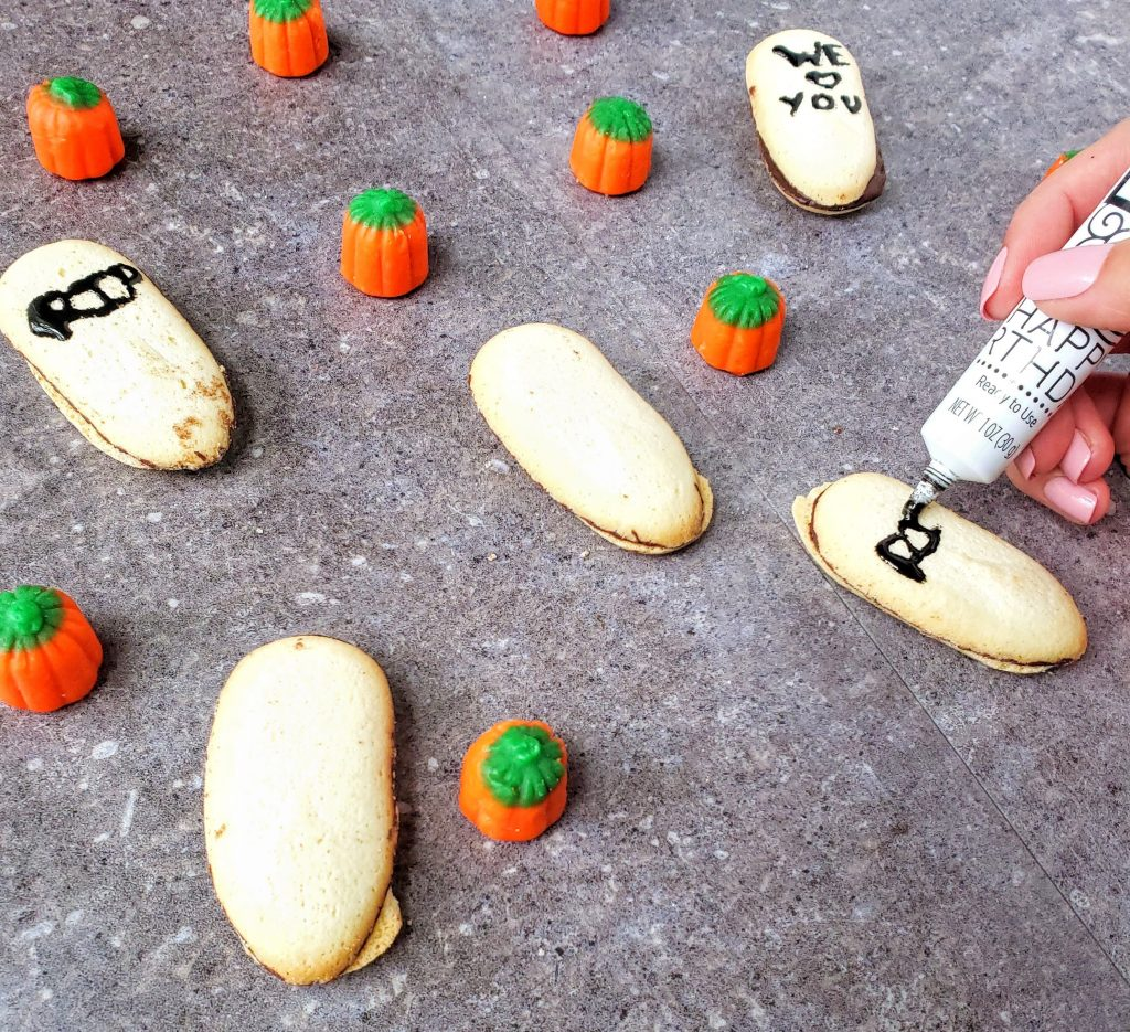 decorating milano cookies to make tombstones for easy chocolate graveyard cake
