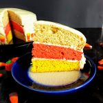 slice of candy corn cake with full cake in the background