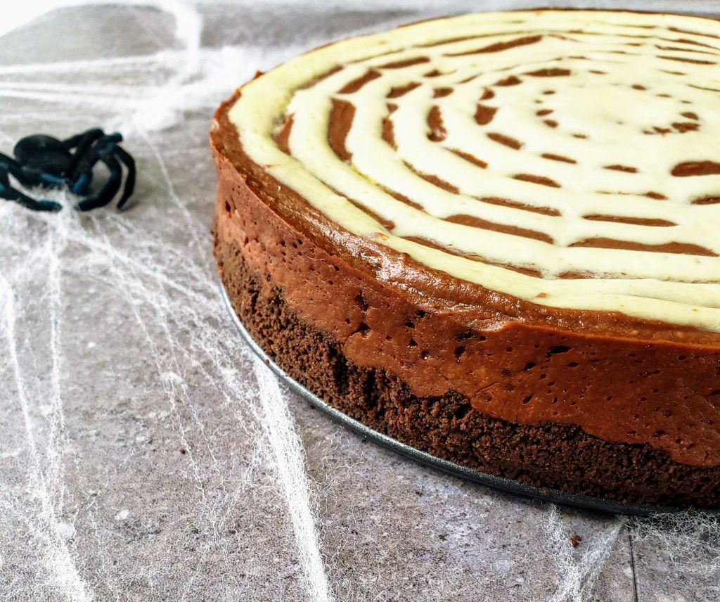 side view of spiderweb chocolate peanut butter cheesecake with a spider off to the side