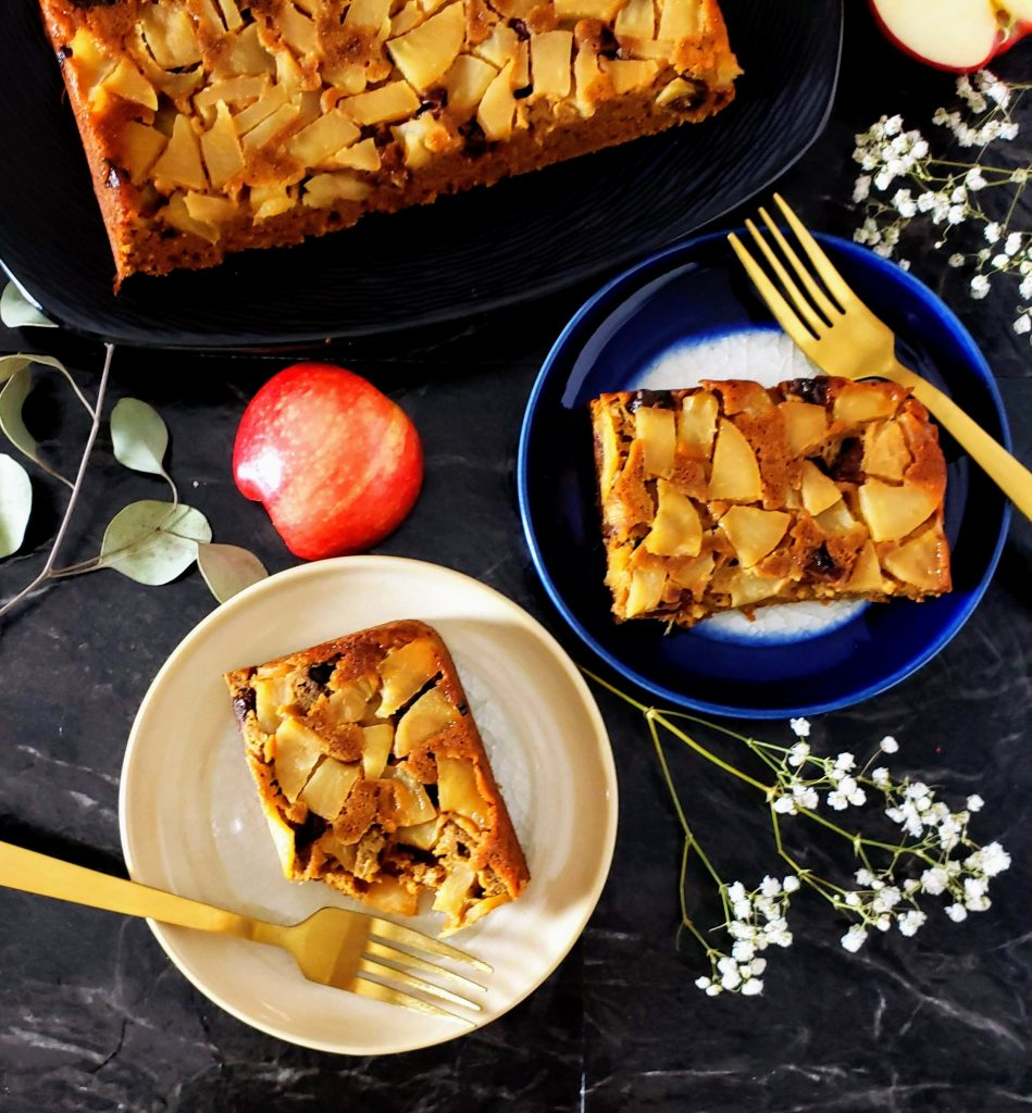 top down view of two slices of healthy apple upside down cake with gold forks on the plates