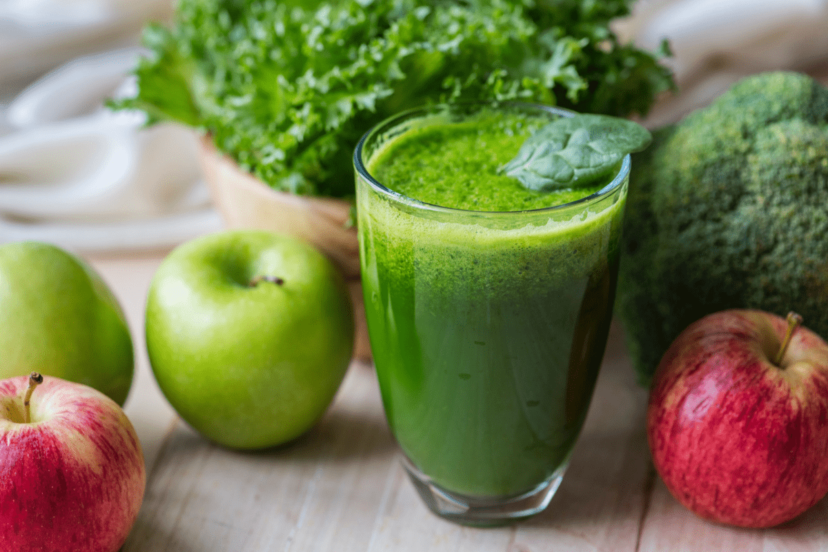 glass of green juice with apples around it