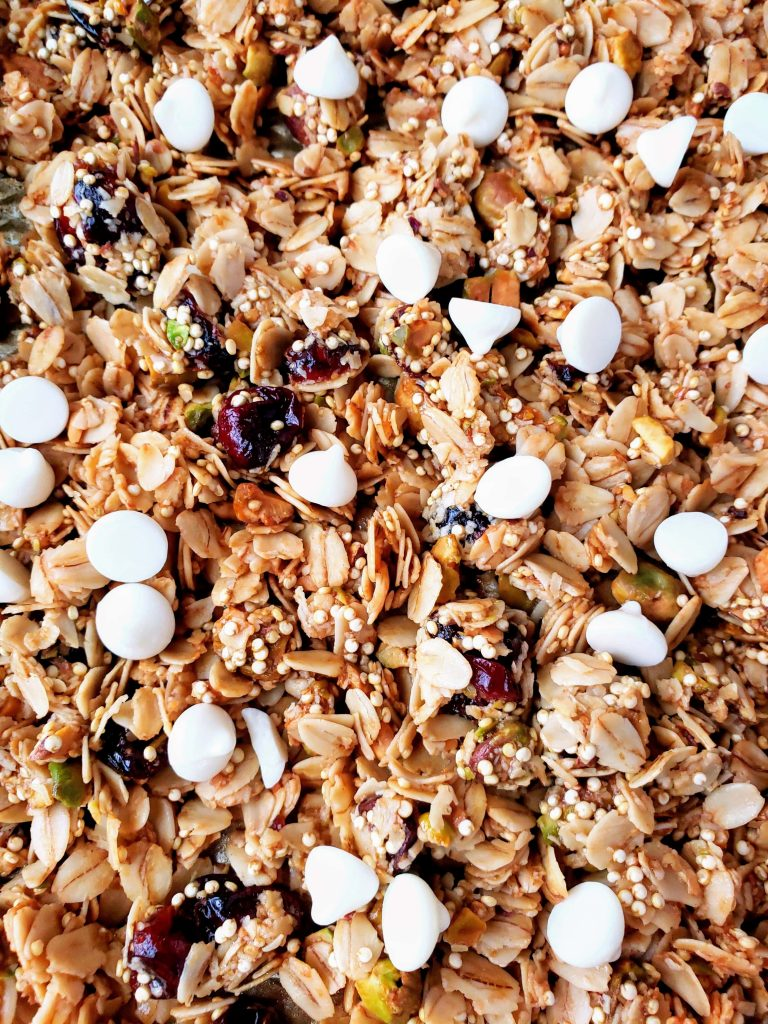 white chocolate chips on top of warm healthy cranberry orange pistachio granola
