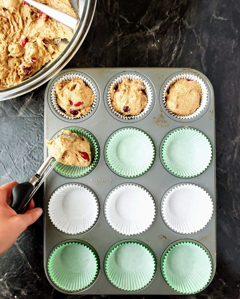scooping healthy cranberry orange batter into muffin cups