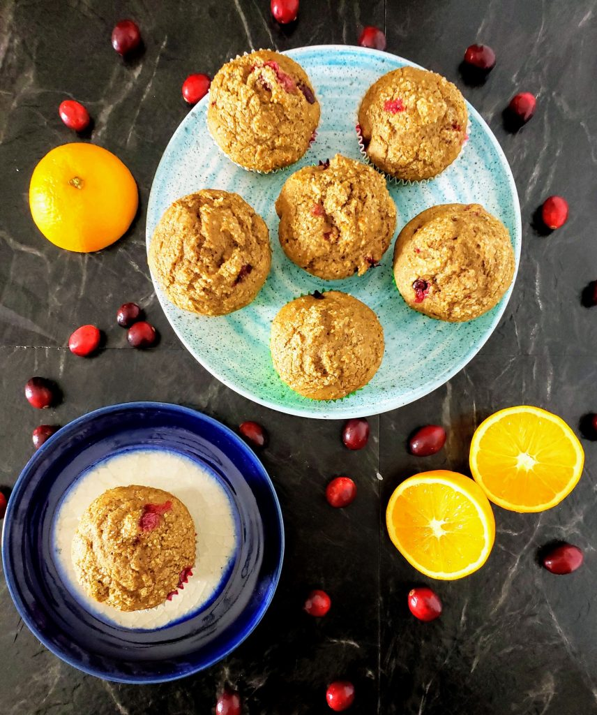 two plates of healthy cranberry orange muffins with sliced oranges on the side