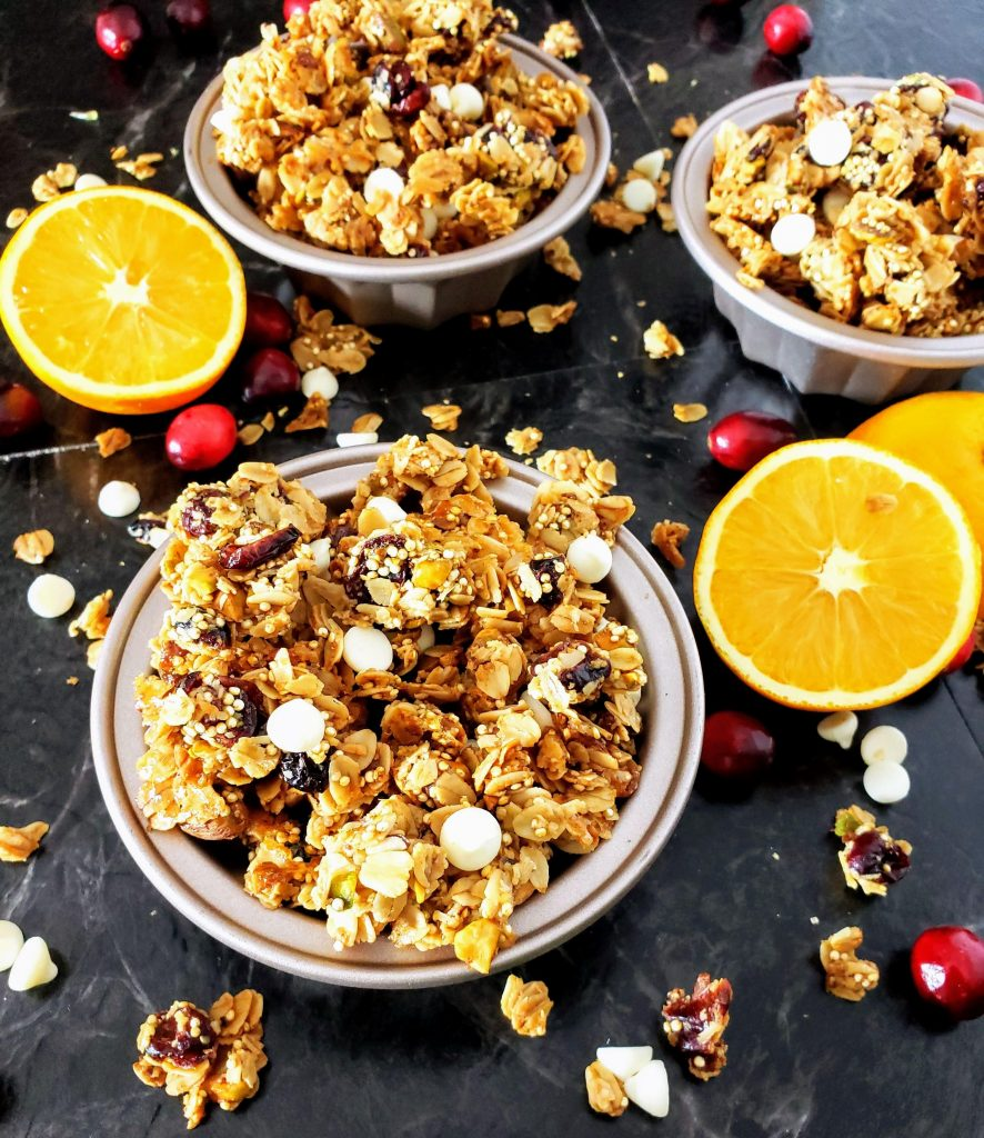 three bowls of healthy cranberry orange pistachio granola and oranges on the side