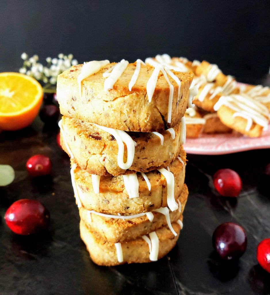 stack of cranberry orange shortbread cookies with a plate of cookies in the background