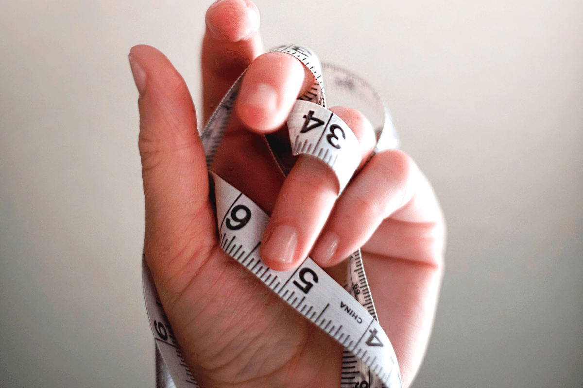 diets don't work: hand wrapped in a tape measure