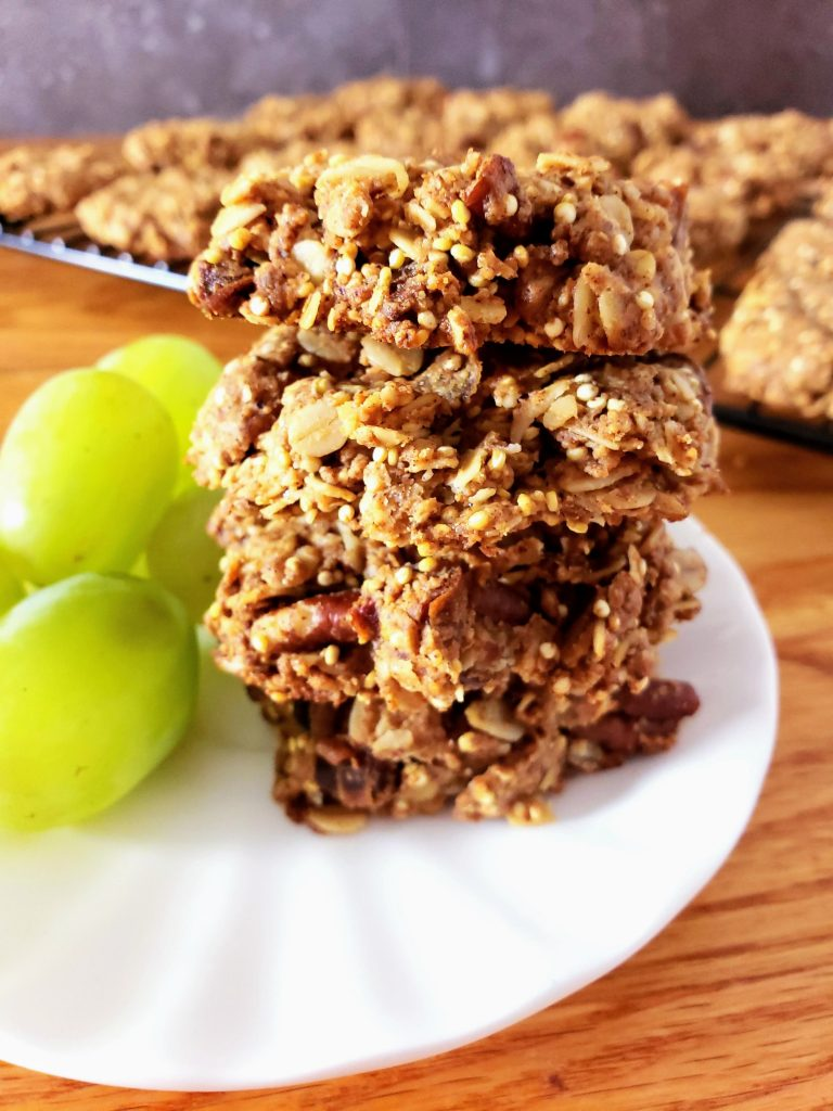 stack of gluten free healthy breakfast cookies on a white plate with grapes to the left