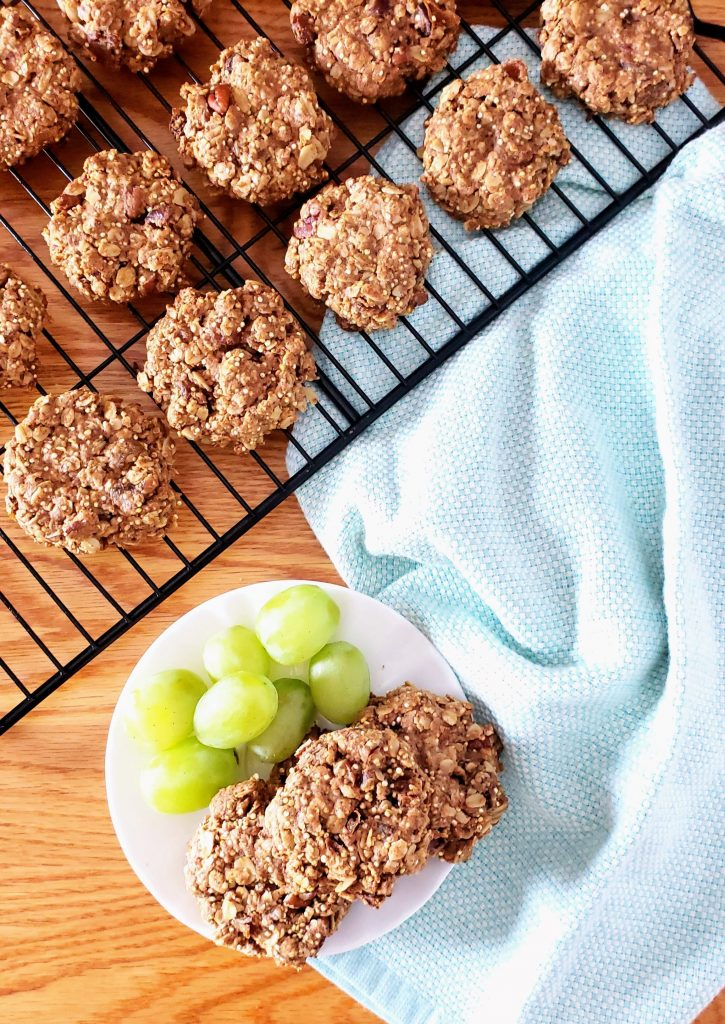 gluten free healthy breakfast cookies on a white plate with grapes and more cookies on a wire cooling rack